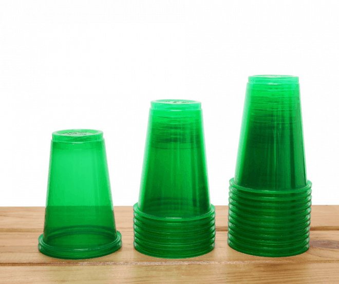 Green Plastic Cups stacked on brown stained table - Fun Family Christmas Games