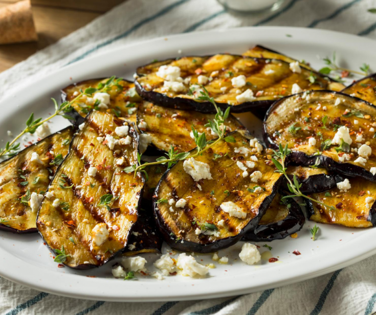 Sliced Eggplant Grilled and Topped With Feta Cheese on white platter