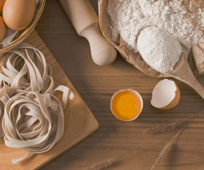Making pasta - flour, rolling pin and pasta on brown cutting board