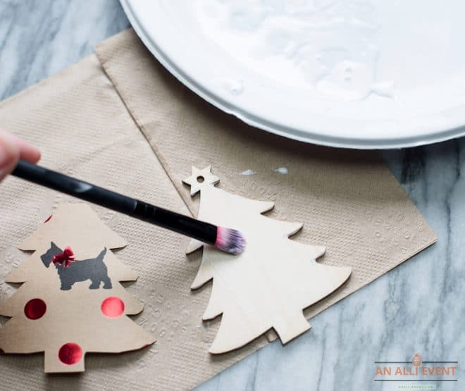 Use Mod Podge with a paint brush to brush over the wooden tree ornament