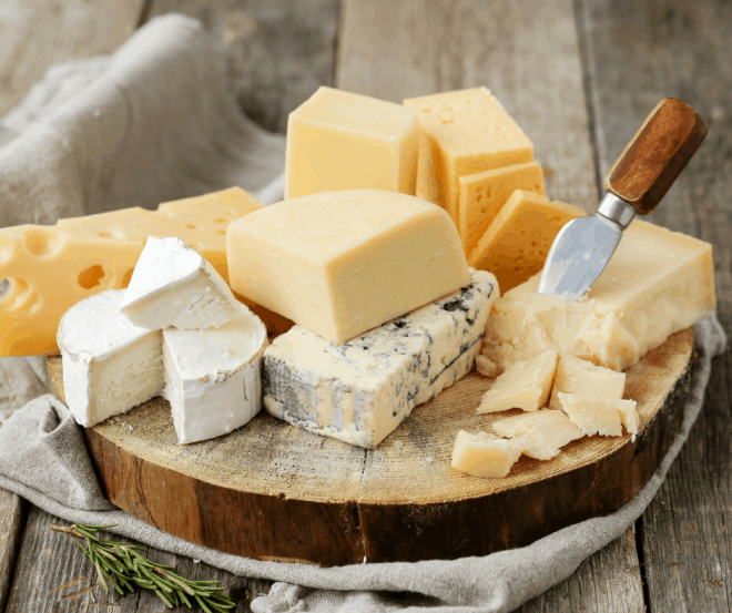 Different types of cheese on a round cheese platter