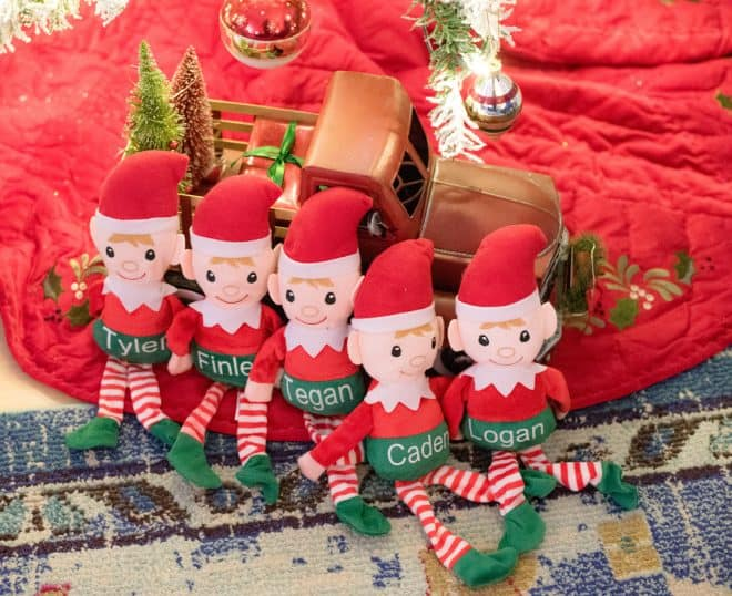 Elf dolls under the Christmas Tree in front of a red truck