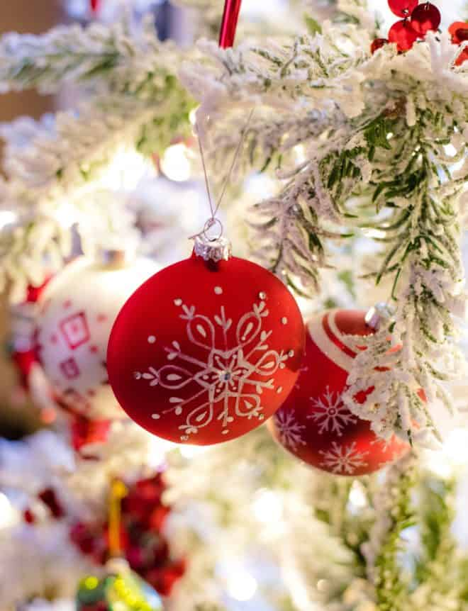 Red Ornament on Flocked Tree - Close Up Shot