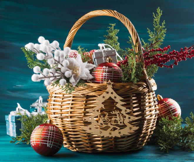 wicker gift basket filled with berries, Christmas ornaments and greenery