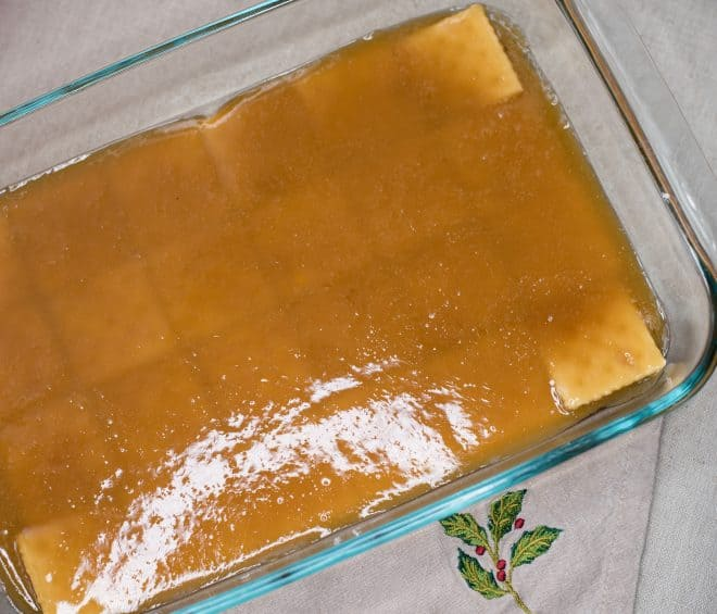 Toffee mixture poured over saltine crackers in 13x9 glass baking dish - to make Chocolate Crunch Candy