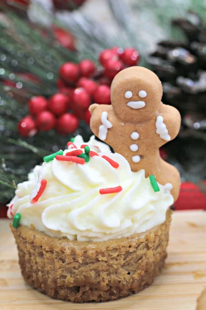 Mini Gingerbread Cheesecake topped with whipped cream, red and white sprinkles and an edible gingerbread man