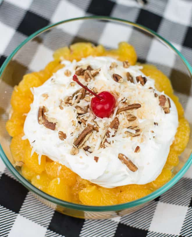 Old fashioned ambrosia in glass bowl topped with whipped cream, pecans and a cherry