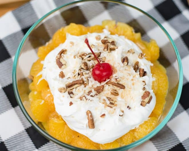 Old Fashioned Ambrosia - layer of orange segments, whipped cream, coconut, pecans and a cherry in a glass bowl