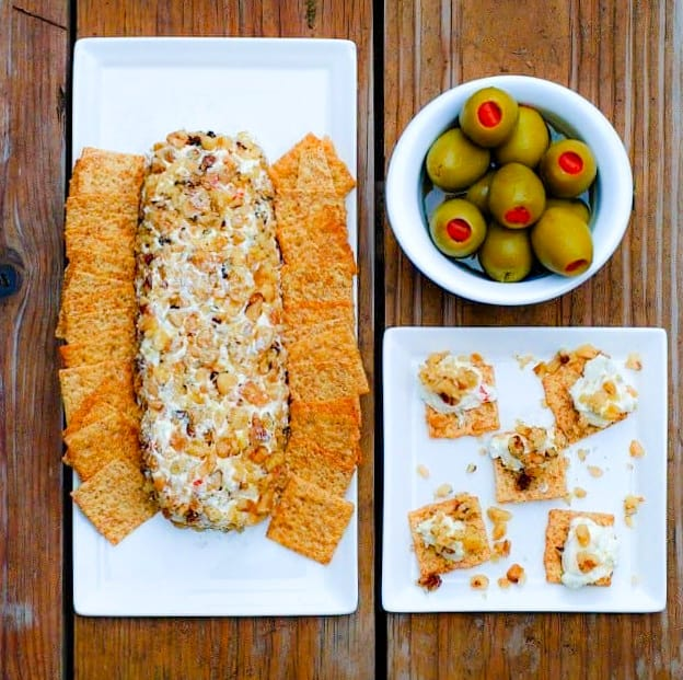 Walnut Olive Cheese Log on white serving platter surrounded by crackers and a bowl of Spanish olives