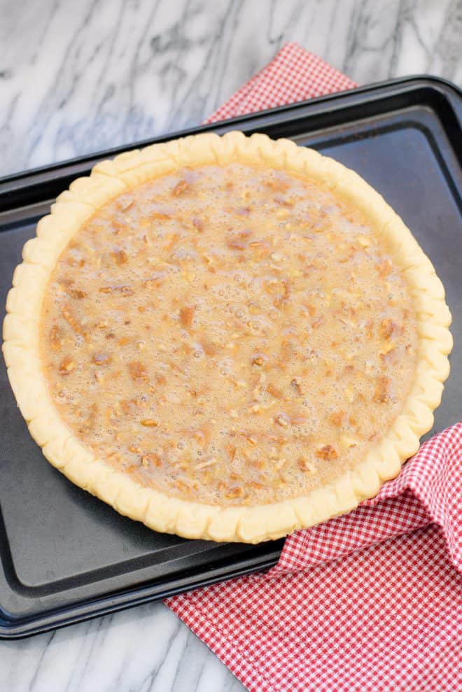 caramel pecan pie filling in pie shell before baking, placed on a dark brown cookie sheet
