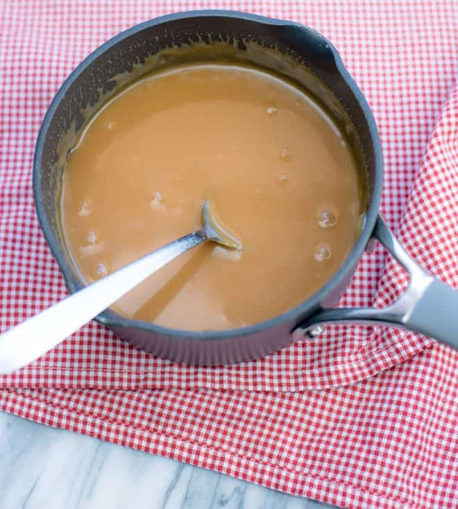 a small saucepan with melted caramels and a spoon to stir