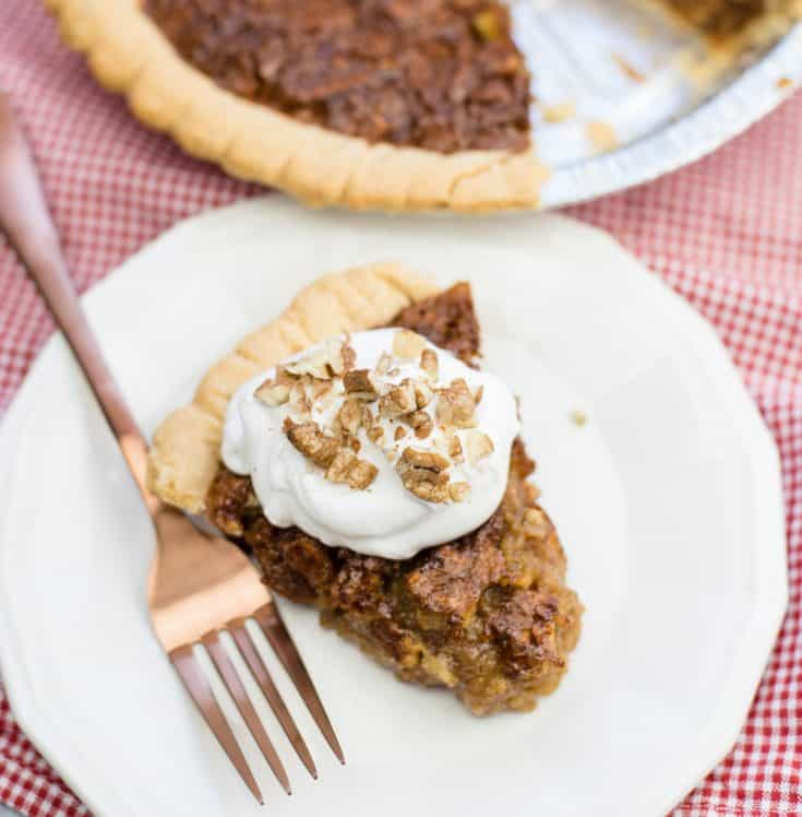 Slice of Caramel Pecan Pie on white serving plate with rose gold fork and whole pie in the background
