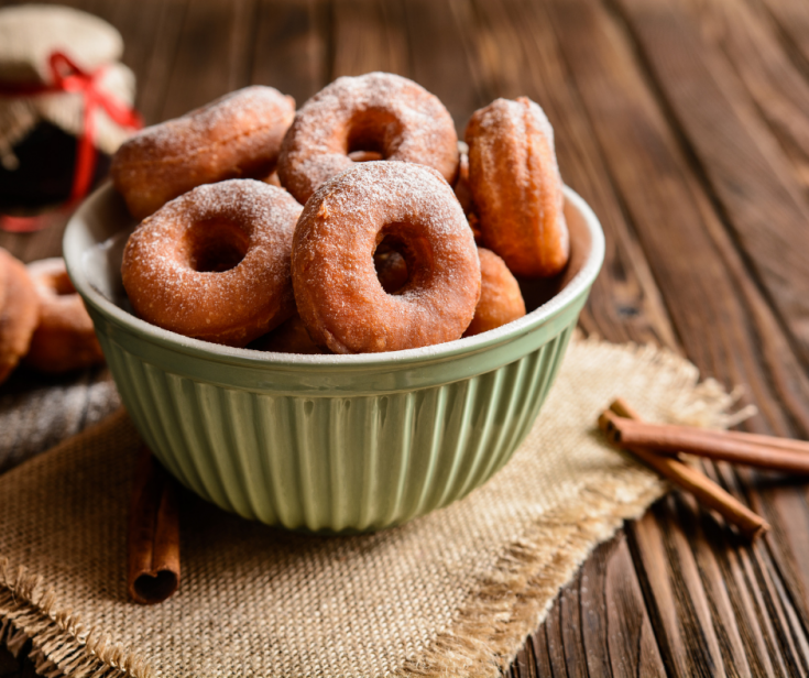 Doughnuts in green bowl on wood table