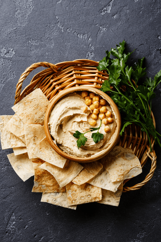 A bowl of easy homemade hummus in a brown basket surrounded by toasted pita chips