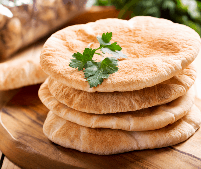 rounds of toasted pita bread rounds on a cutting board