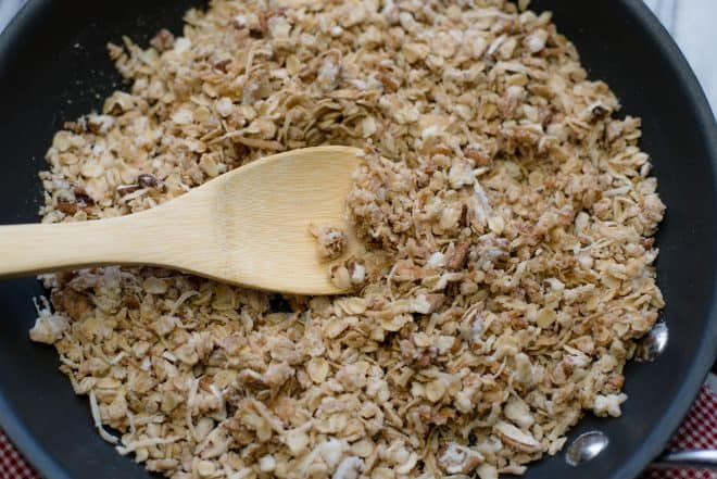 Granola in a skillet with a wooden spoon
