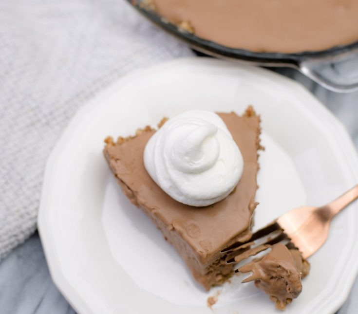 A closeup photo of a slice of chocolate pie on a white serving plate with a rose gold fork