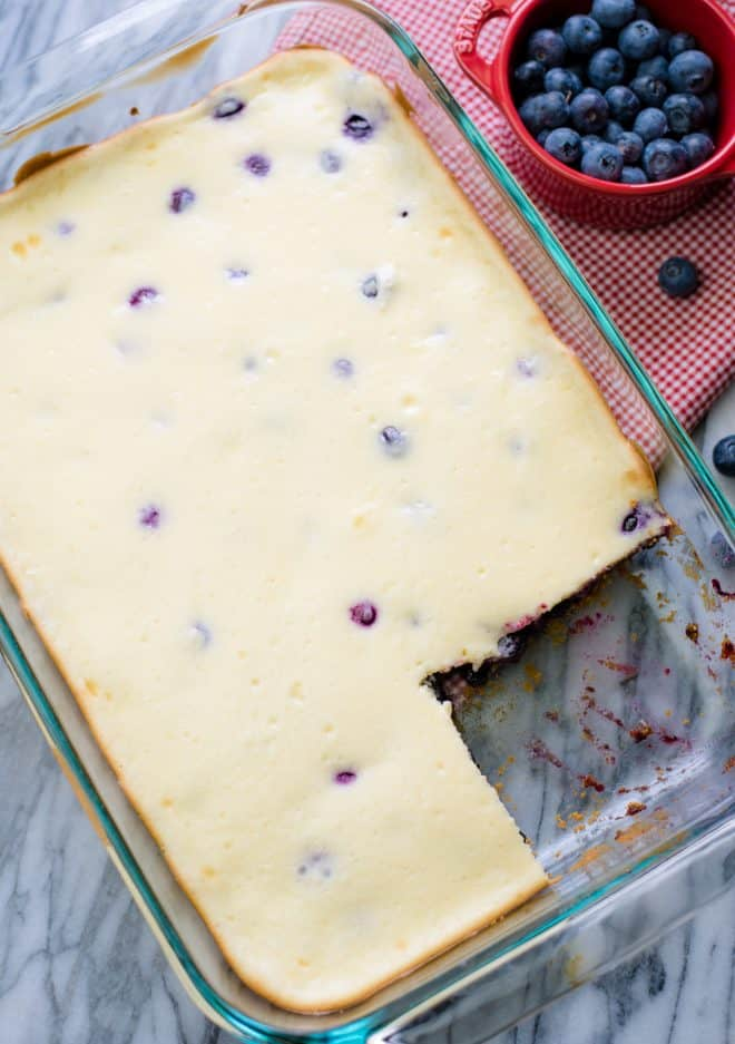 Blueberry Cheesecake Bars in a 13x9 pan with a bowl of blueberries beside the pan