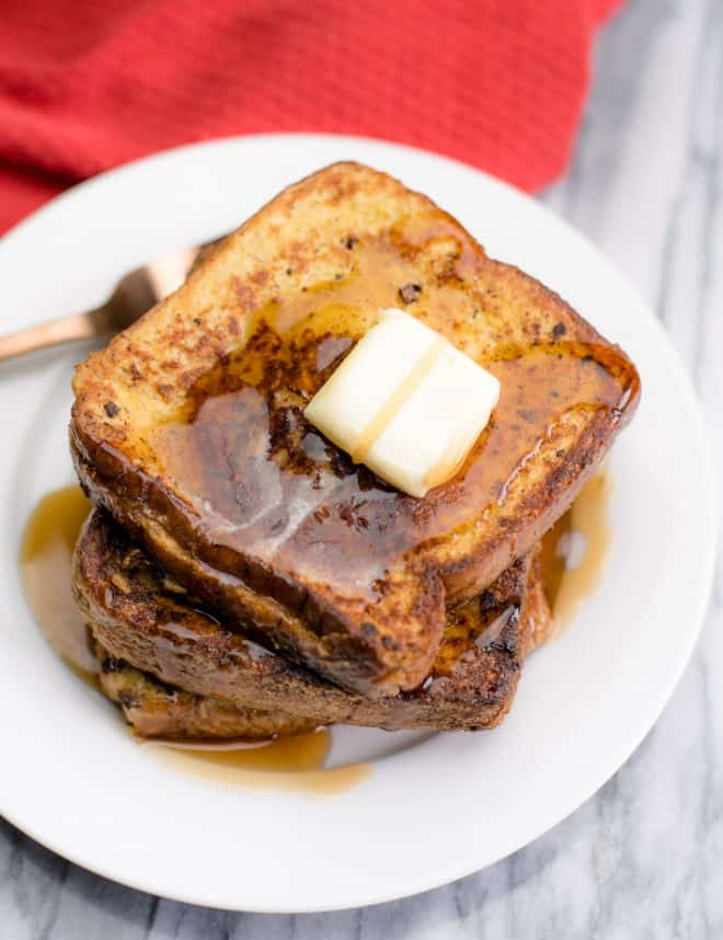 Stuffed French Toast on a white plate with a pat of butter and syrup
