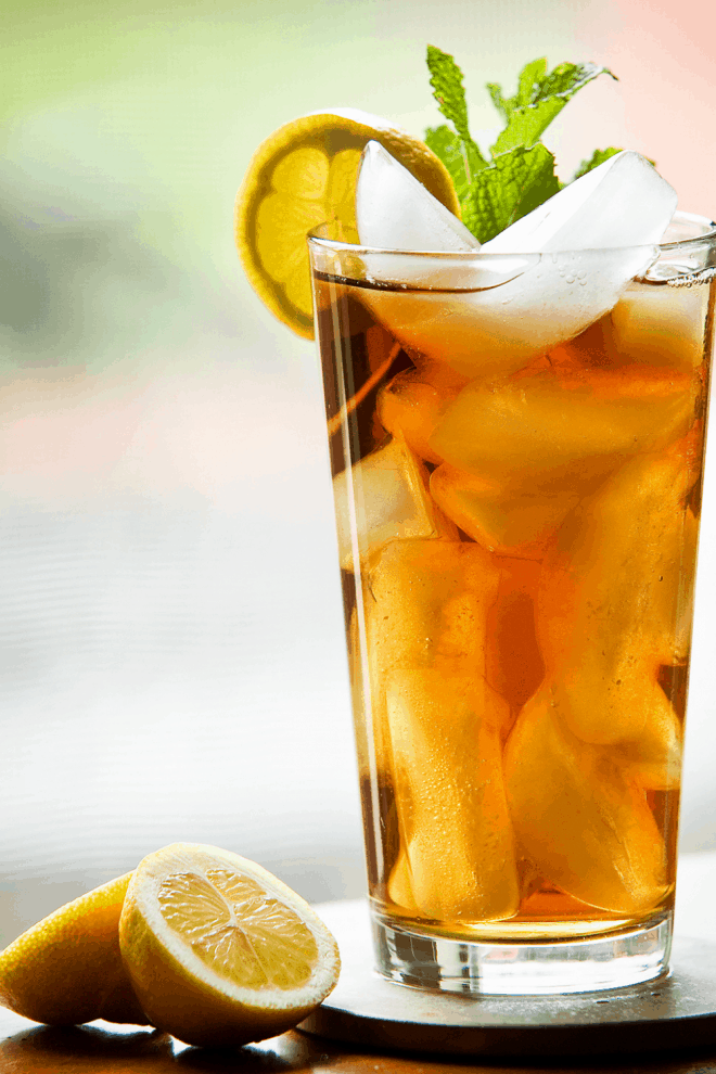 southern sweet tea in a tall glass over ice and garnished with mint and lemon slices