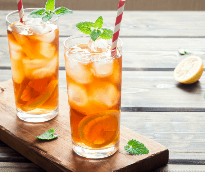 two glasses of sweet tea over ice on a wooden table. The glasses of iced tea are garnished with lemon slices and mint leaves