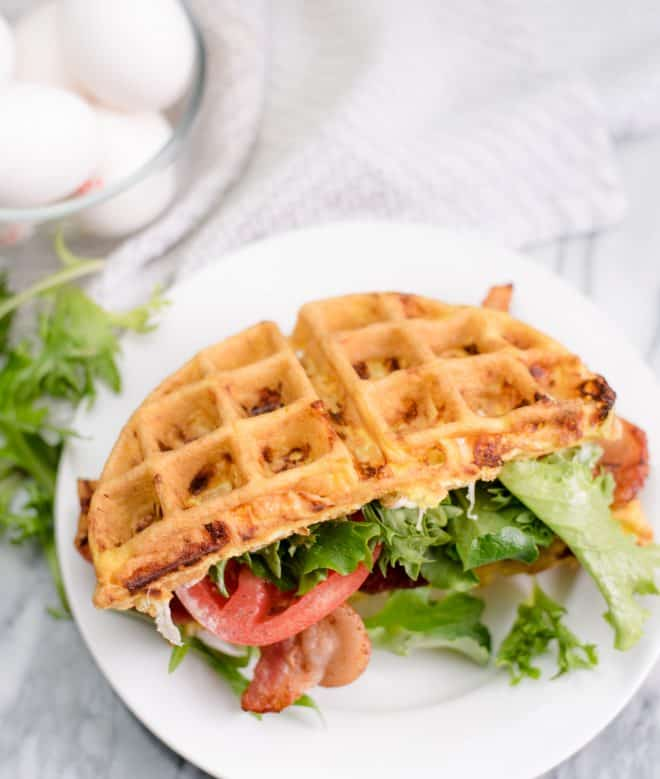BLT Chaffle on white plate with eggs in the background