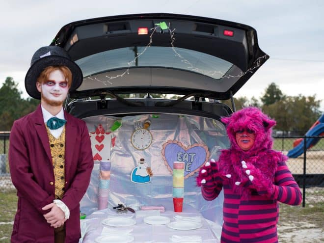 The Mad Hatter in front of a trunk decorated for Trunk or Treat