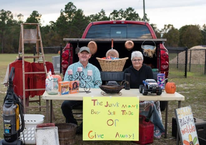 junk man trunk or treat with junk hanging and a sign that says junk, sell, buy or give away