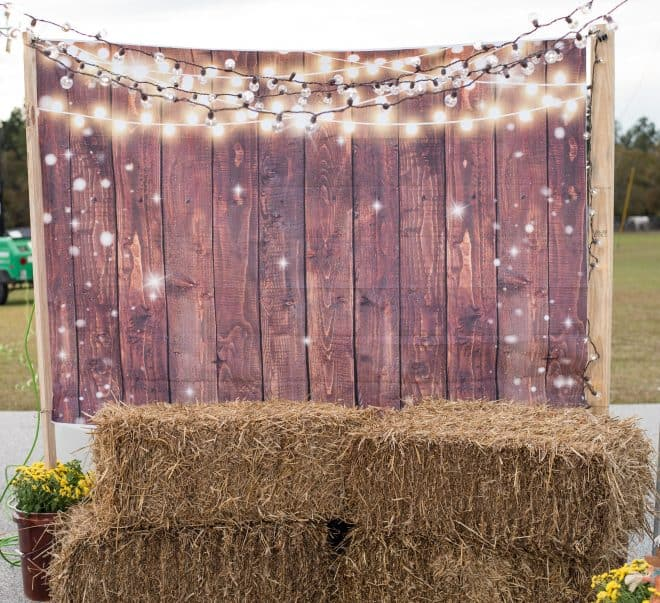trunk or treat photo booth with string lights, wood plank backdrop and hay bales to sit on