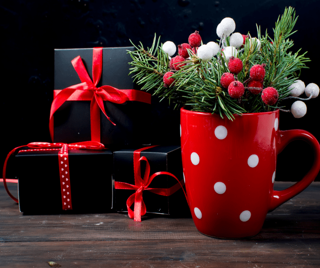 red Christmas mug with Christmas decorations and wrapped Christmas gifts in the background