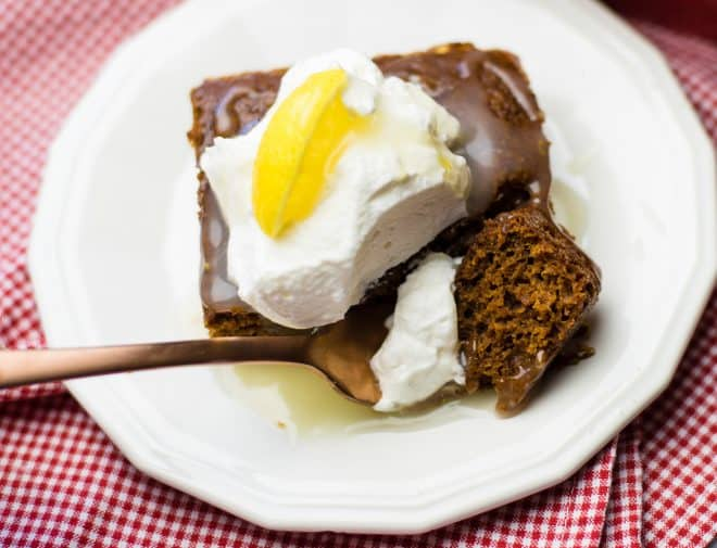 Close Up Photo of a serving of gingerbread on a white dessert plate topped wth lemon sauce and whipped topping