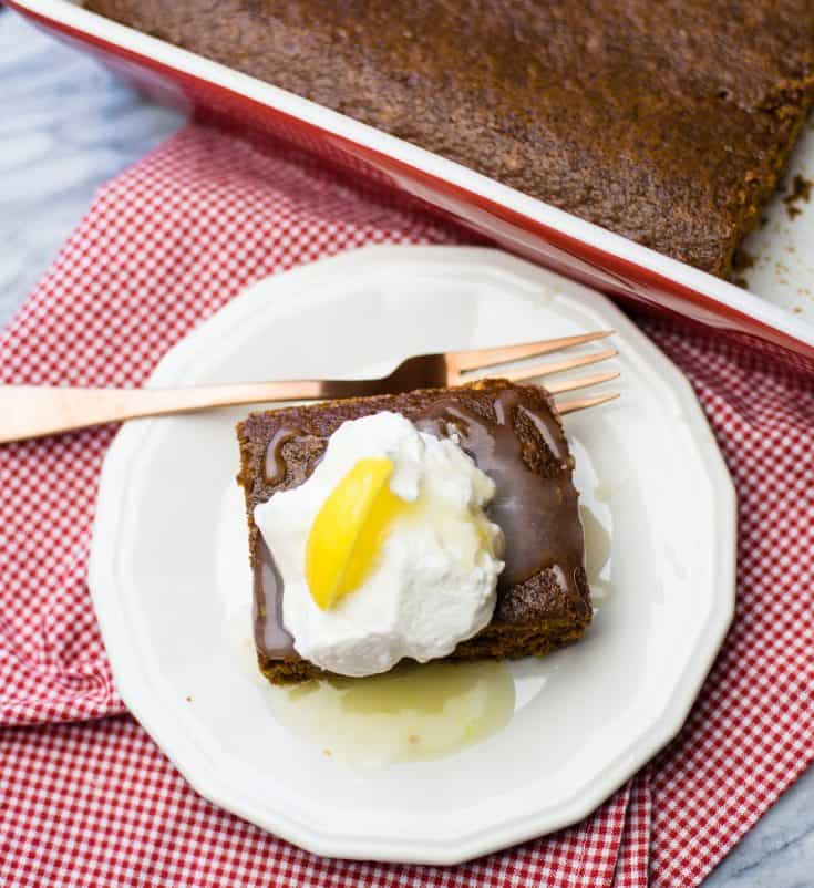 easy gingerbread in a 13x9 pan beside a white dessert plate with a square of gingerbread topped with lemon sauce and whipped cream